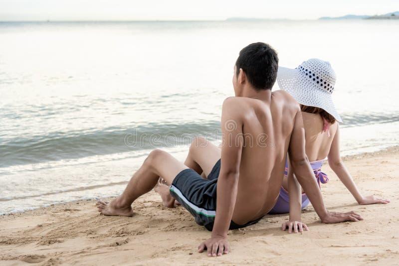 一起坐沙子海海滩和看对h的年轻夫妇 免版税图库摄影