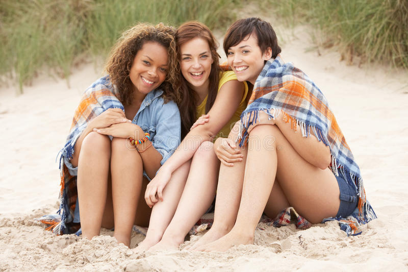 一起坐海滩的女孩 库存图片