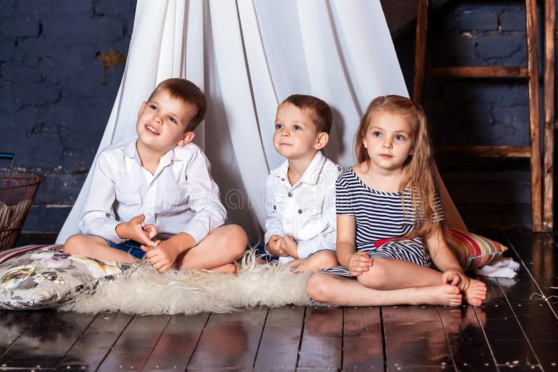 一起坐男孩女孩兄弟姐妹的孩子其次看起来蓝眼睛坐白色三重奏三地板夸大手表顶楼顶楼 免版税图库摄影