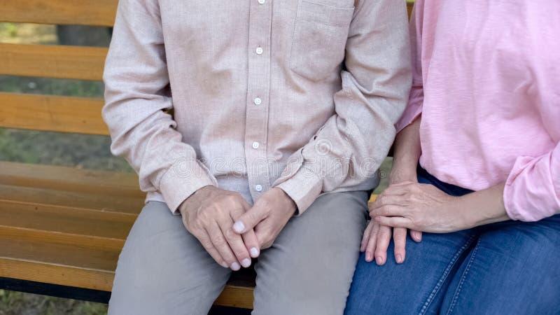 一起坐长凳室外,年长夫妇日期的祖父和祖母 免版税库存照片