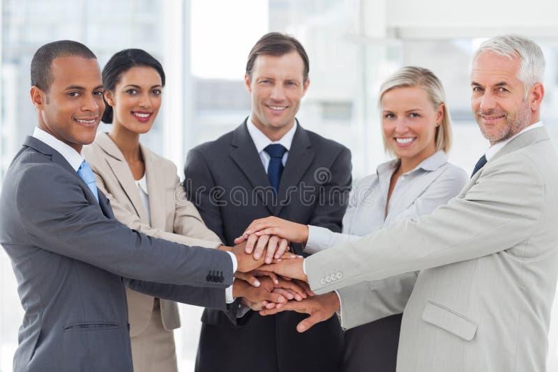 一起堆他们的手的小组微笑的商人 免版税库存照片