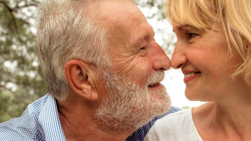 一起好的年长夫妇在夏天公园,愉快的资深夫妇走在公园的,幸福生活 库存照片