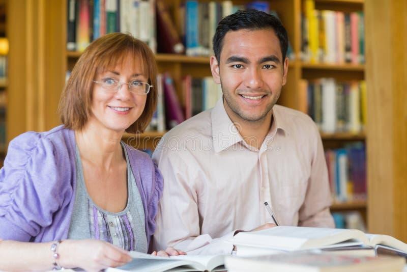 一起学习在图书馆里的成人学生 免版税图库摄影