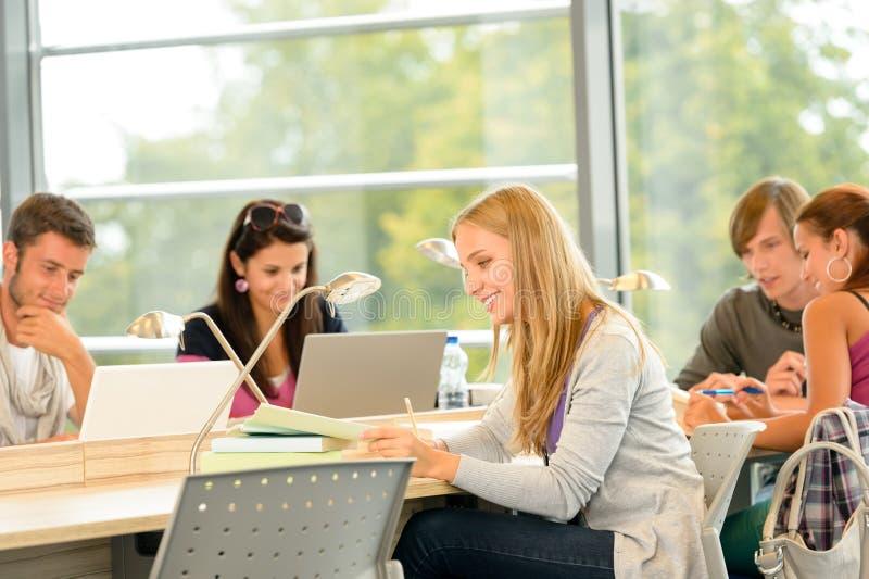 一起学习在图书馆里的高中学员 库存照片