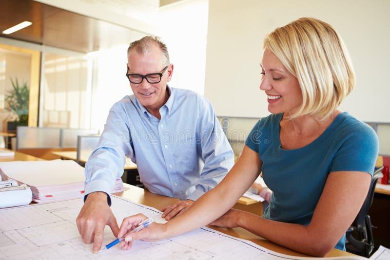 一起学习计划的建筑师在现代办公室 免版税库存图片