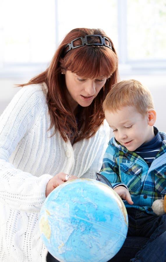 一起学习逗人喜爱的地球孩子的母亲 免版税库存照片