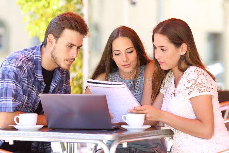 一起学会在咖啡馆的三名学生 免版税库存照片