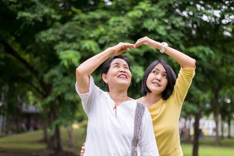 一起小心和支持概念,年长亚裔妇女画象有女儿姿势手心脏的在室外,愉快和smili 免版税库存图片