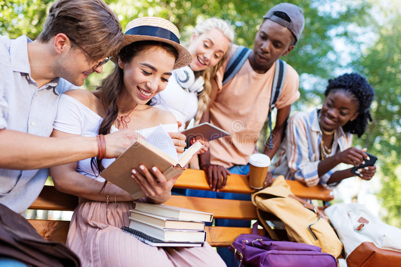 一起年轻不同种族的学生阅读书在长凳在公园 免版税库存照片