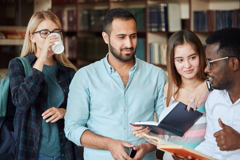 一起年轻多文化朋友看书画象在图书馆里 免版税库存照片