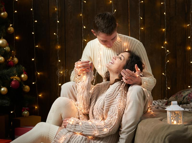 一起年轻夫妇在圣诞灯和装饰,穿戴在白色,在黑暗的木背景,浪漫晚上的杉树, 免版税图库摄影