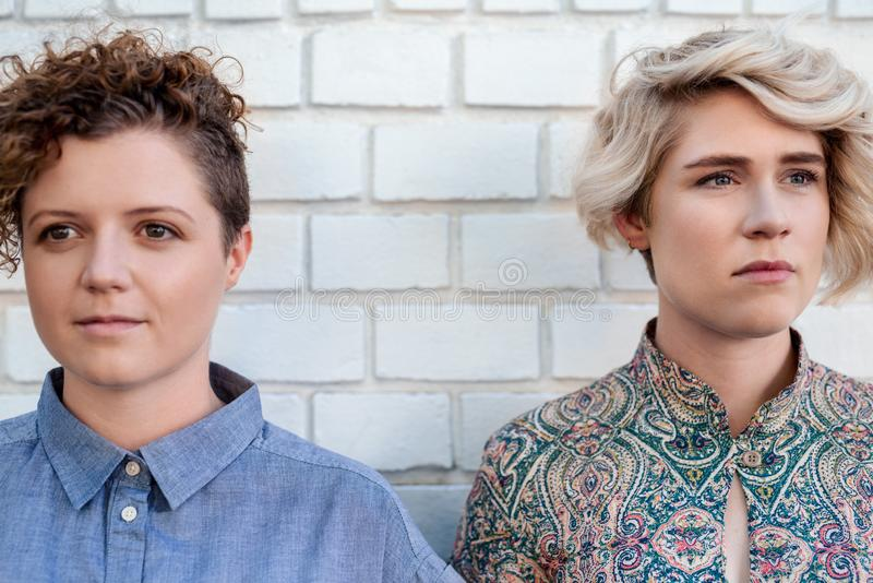 一起年轻女同性恋的夫妇身分在看在不同的方向之外 图库摄影