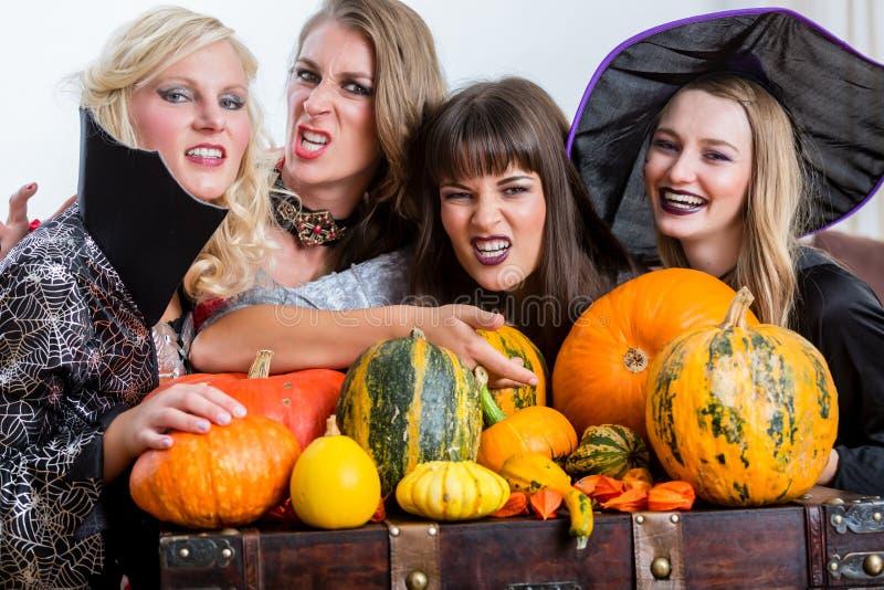 一起庆祝万圣夜的四名快乐的妇女在服装党期间 免版税库存照片