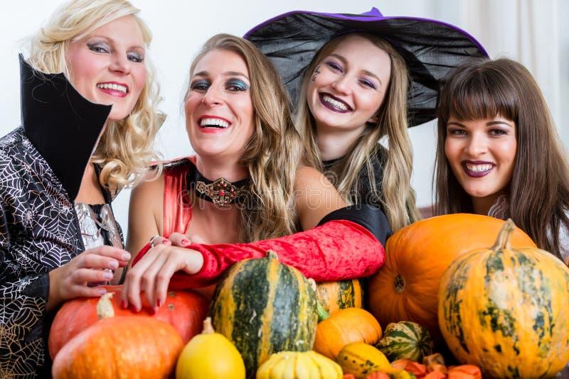 一起庆祝万圣夜的四名快乐的妇女 免版税库存图片