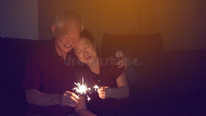 一起庆祝亚洲资深的夫妇在家闪耀烟花s 库存图片