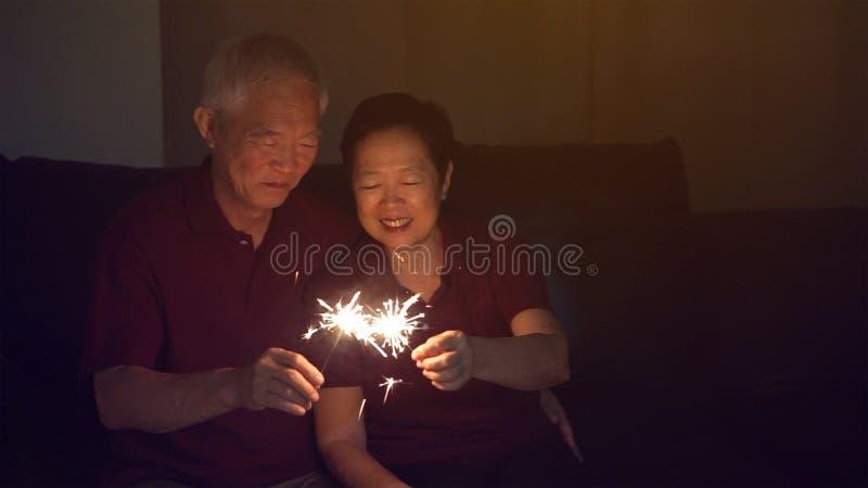 一起庆祝亚洲资深的夫妇在家闪耀烟花s 免版税图库摄影