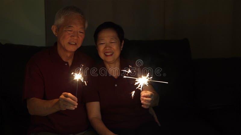 一起庆祝亚洲资深的夫妇在家闪耀烟花s 免版税库存图片