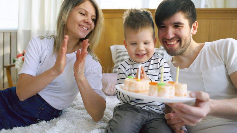 一起庆祝他们的儿子生日的微笑的家庭在吹在蛋糕的蜡烛前 库存照片