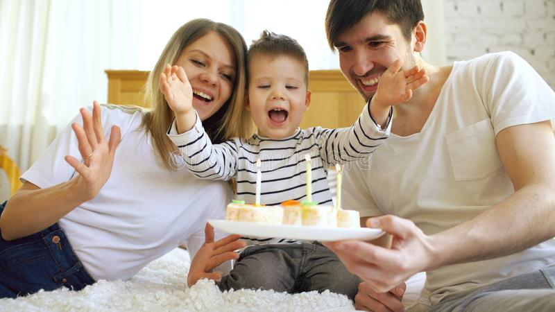 一起庆祝他们的儿子生日的微笑的家庭在吹在蛋糕的蜡烛前 免版税库存图片