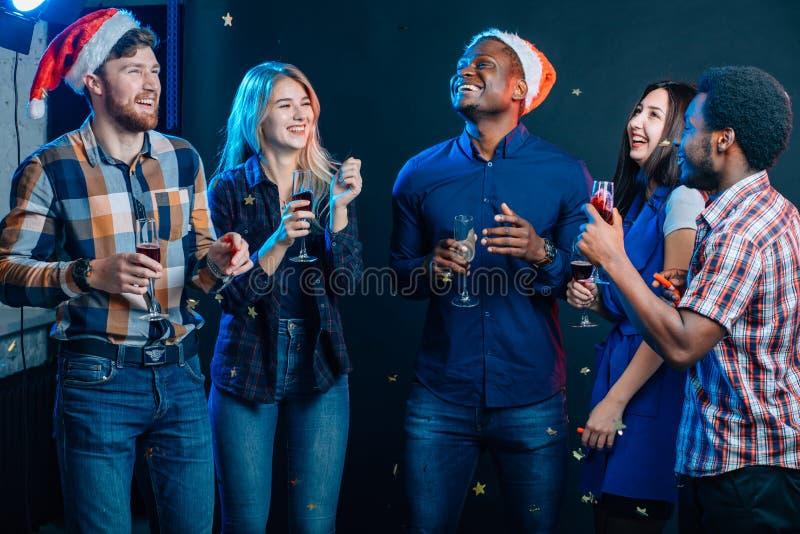 一起庆祝新年 小组圣诞老人帽子的美丽的青年人 免版税图库摄影