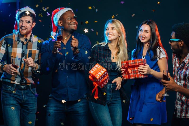 一起庆祝新年 小组圣诞老人帽子的美丽的青年人 免版税库存照片
