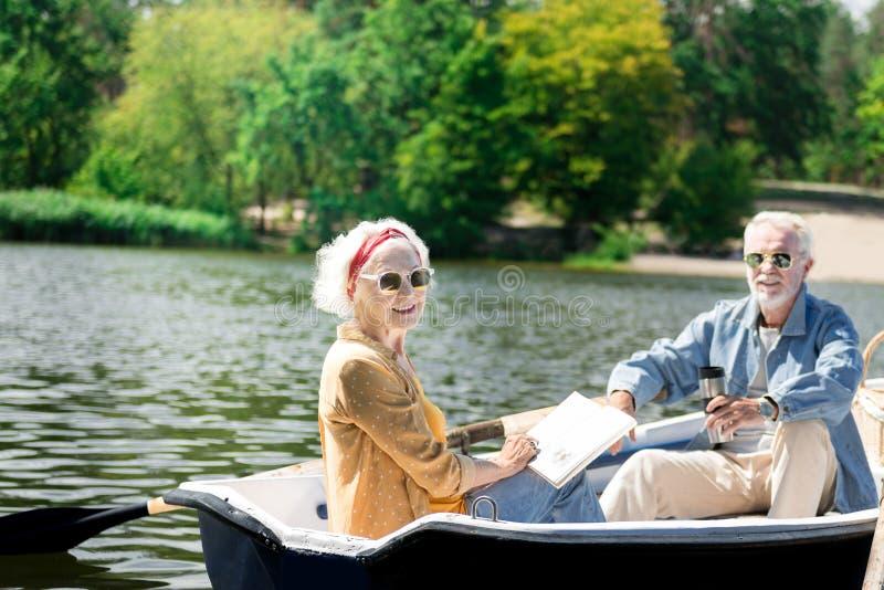 一起微笑和享受划船的快乐的领抚恤金者 免版税库存照片