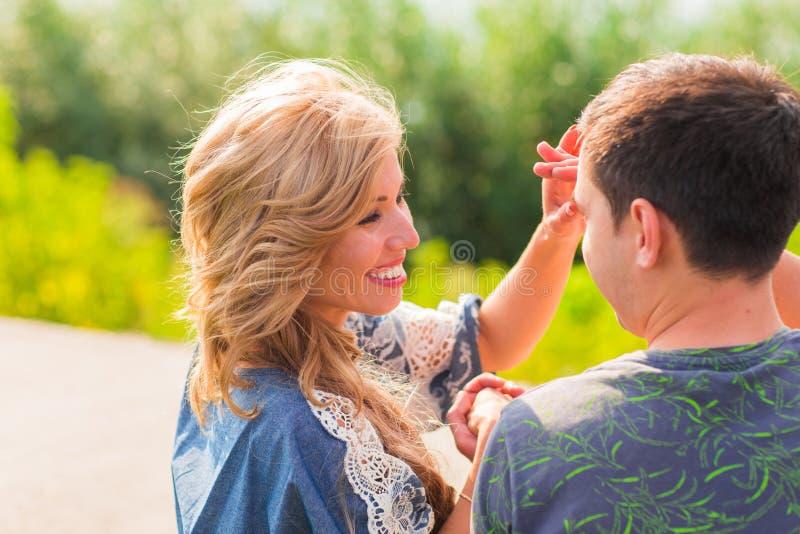 一起微笑室外一对美好的年轻的夫妇的画象- 免版税库存照片