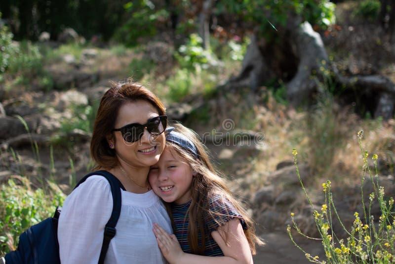 一起微笑,当站立在森林前面在公园时的拉提纳妇女和女儿 图库摄影