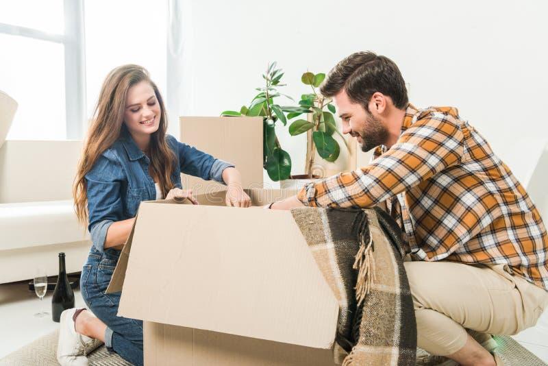 一起打开纸板箱的微笑的夫妇在新家移动 库存图片