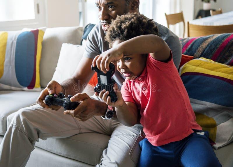 一起打比赛的爸爸和儿子在客厅 免版税图库摄影