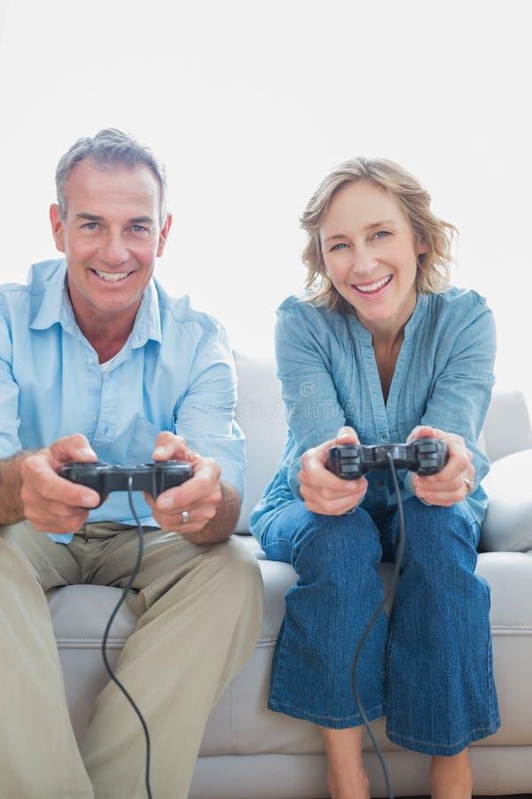 一起打电子游戏的微笑的夫妇在长沙发 免版税图库摄影