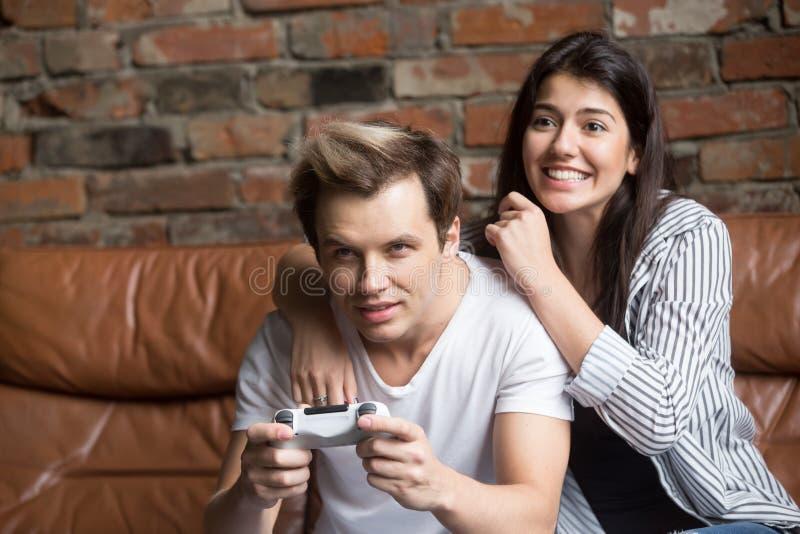 一起打电子游戏的激动的夫妇在家 免版税库存照片