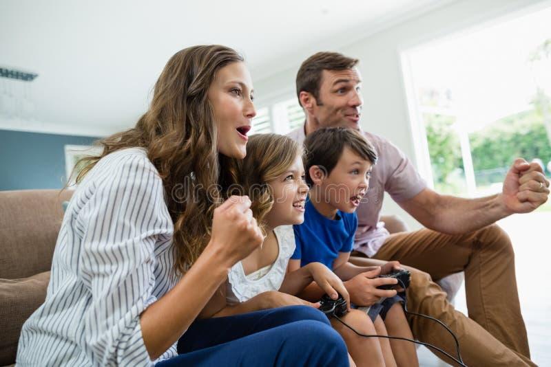 一起打电子游戏的激动的家庭在客厅 库存照片