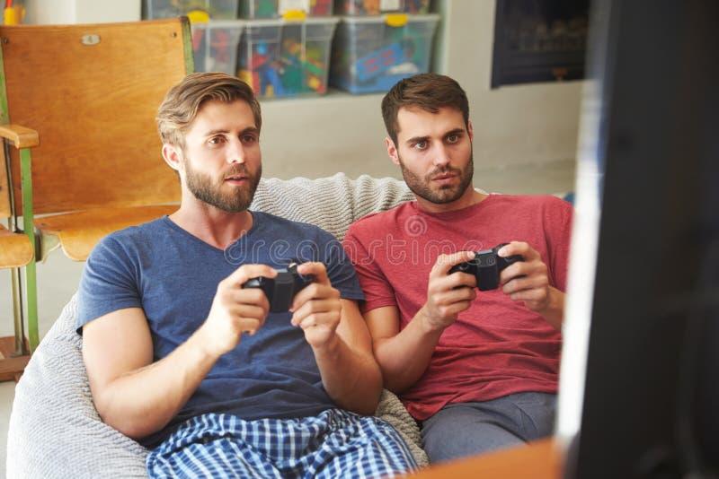 一起打电子游戏的睡衣的两个男性朋友 图库摄影