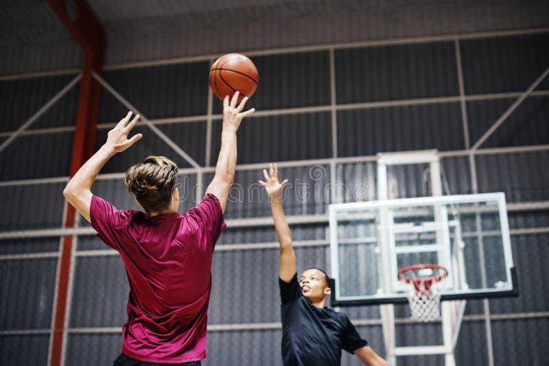 一起打篮球的两个十几岁的男孩在法院 免版税库存图片