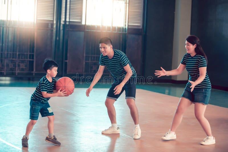 一起打篮球的亚洲家庭 一起花费业余时间的愉快的家庭在度假 库存图片