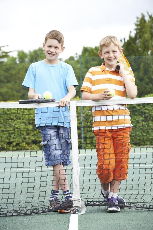 一起打网球的两个男孩画象  免版税库存照片
