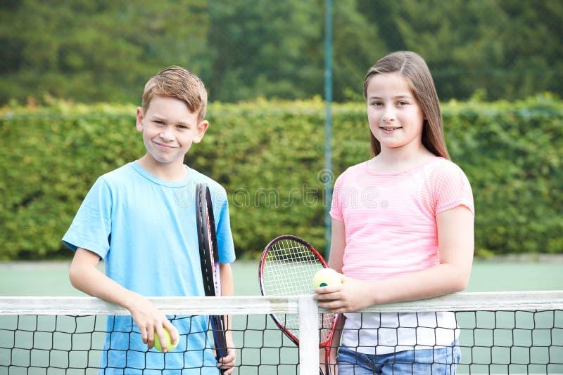 一起打网球的男孩和女孩画象  库存照片