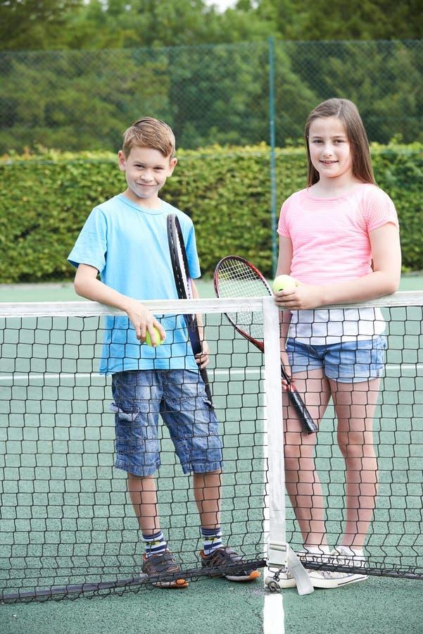 一起打网球的男孩和女孩画象  库存图片