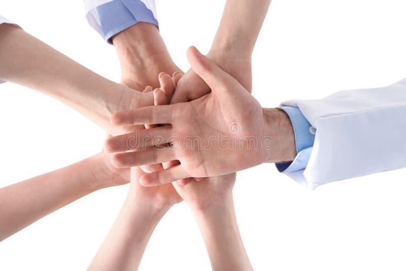 一起把手放的医生队在白色背景,特写镜头上 图库摄影
