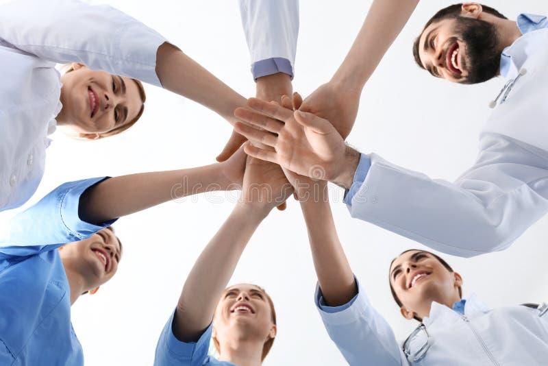 一起把手放的医生队在白色背景,特写镜头上 库存图片