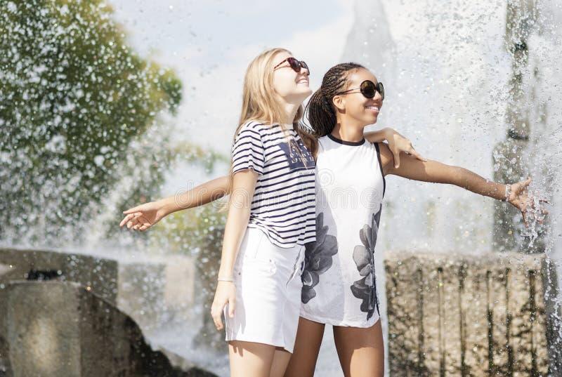 一起拥抱两个少年的女朋友 摆在反对喷泉在公园户外 库存照片