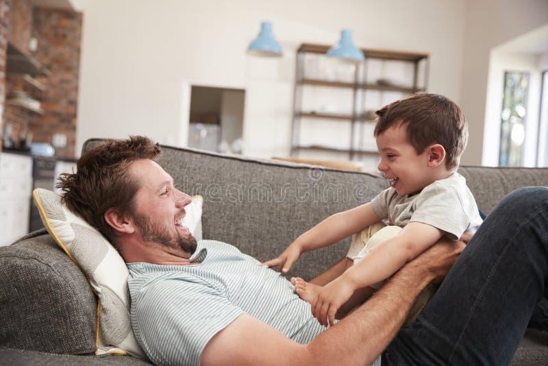一起拥抱在沙发的父亲和儿子 图库摄影