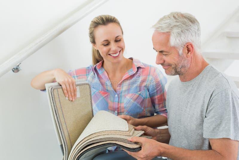 一起挑选地毯样品的愉快的夫妇 库存照片