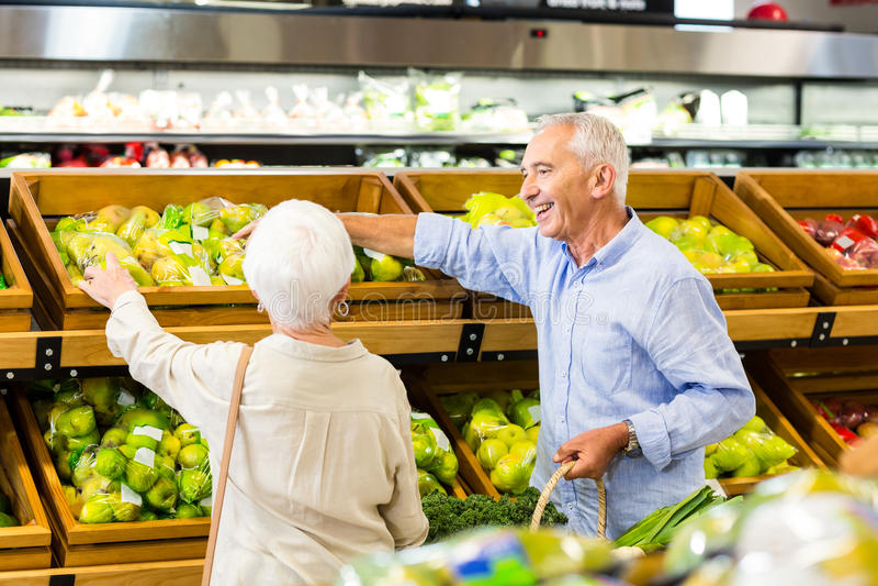 一起挑选果子的资深夫妇 免版税库存照片