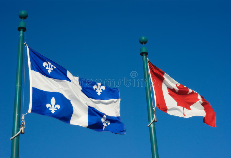 一起振翼在风的魁北克和加拿大旗子在蓝天 图库摄影