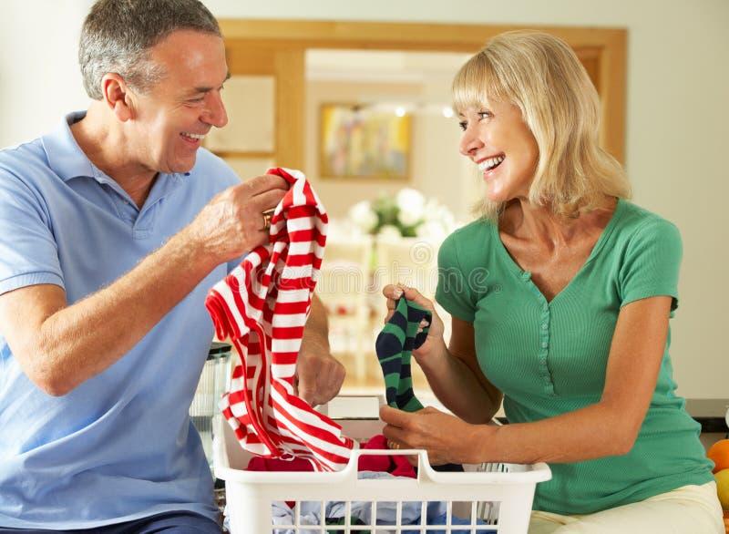 一起排序洗衣店的高级夫妇 免版税库存图片