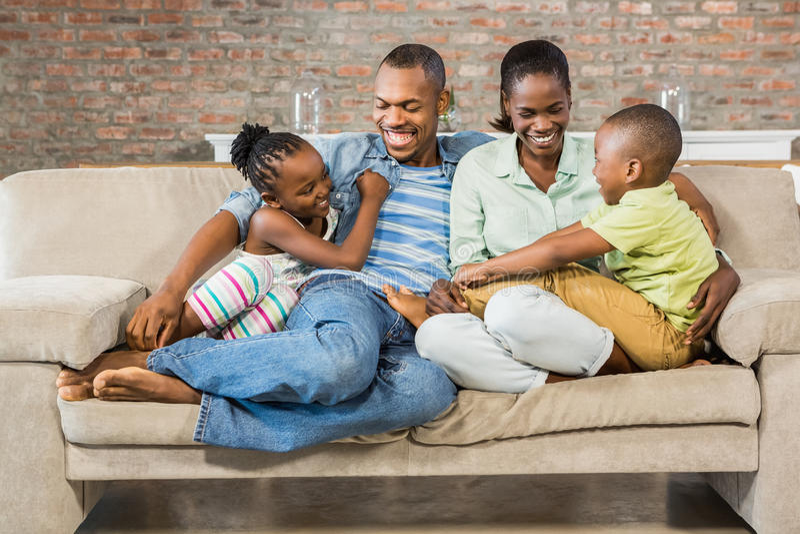 一起摆在长沙发的愉快的家庭 库存照片