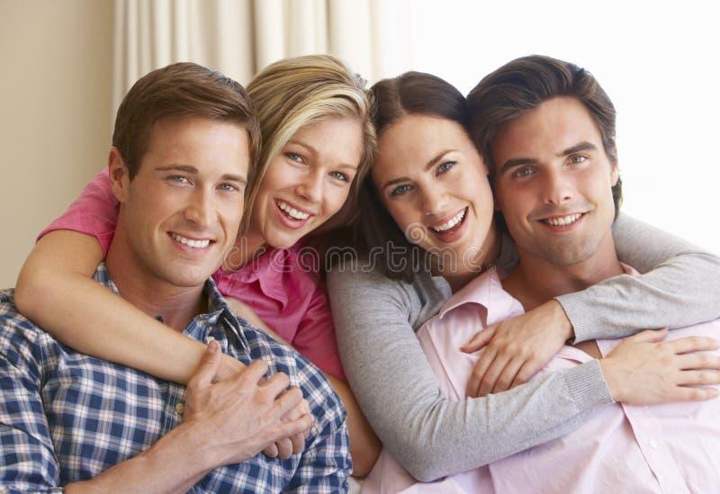 一起放松在沙发的小组年轻朋友在家 库存图片