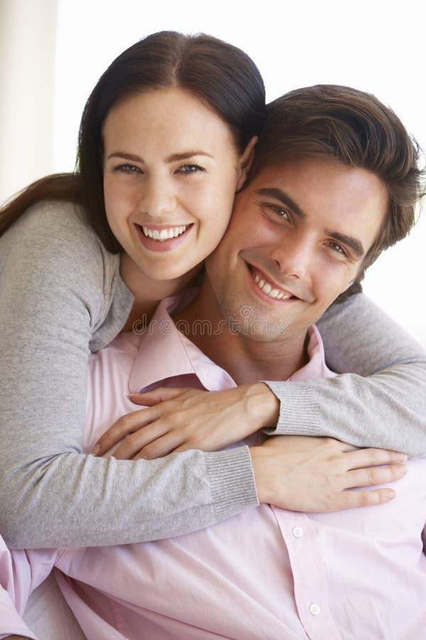 一起放松在沙发的年轻夫妇在家 库存图片